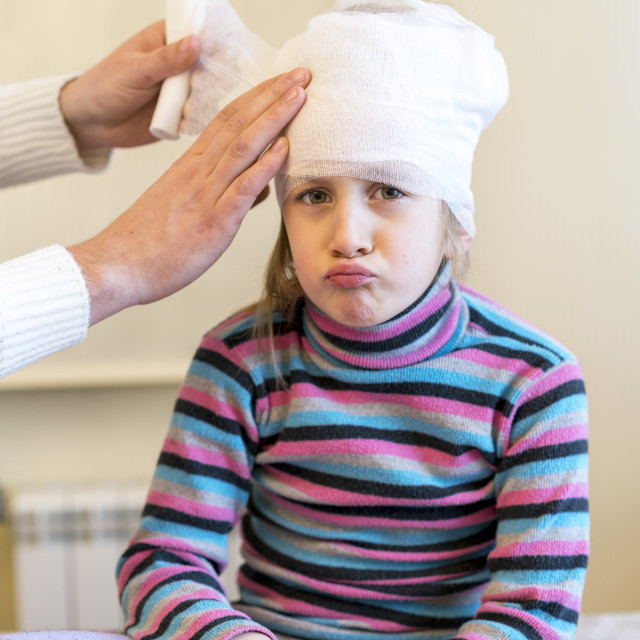 """""""Doctor makes a bandage of young girl's head after plastic surgery"""" stock image"""