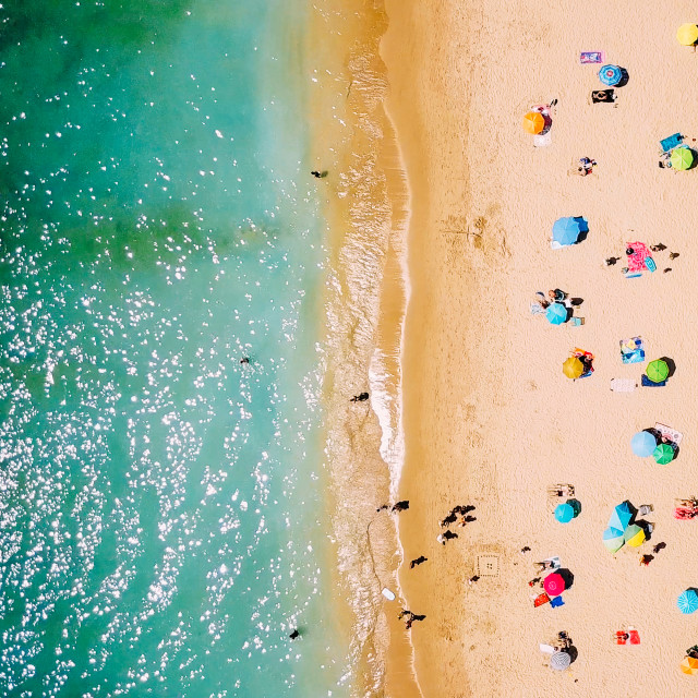 """Aerial View From Flying Drone Of People Crowd Relaxing On Beach In Portugal"" stock image"