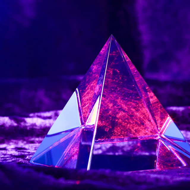 """""""Optical glass pyramid lit with a red laser beam and sat on purple velvet material"""" stock image"""