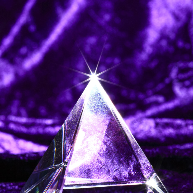"""""""Optical glass pyramid lit from below and sat on purple velvet material"""" stock image"""