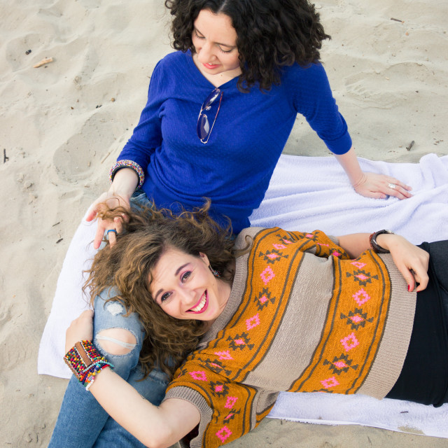 """""""Two girls women laying on towel relaxing sand"""" stock image"""