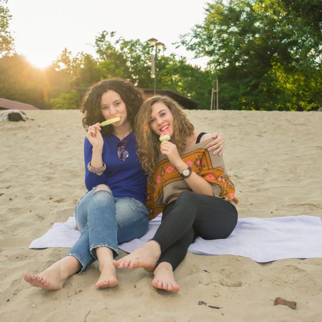 """Two girls women summer hugging eating ice cream"" stock image"