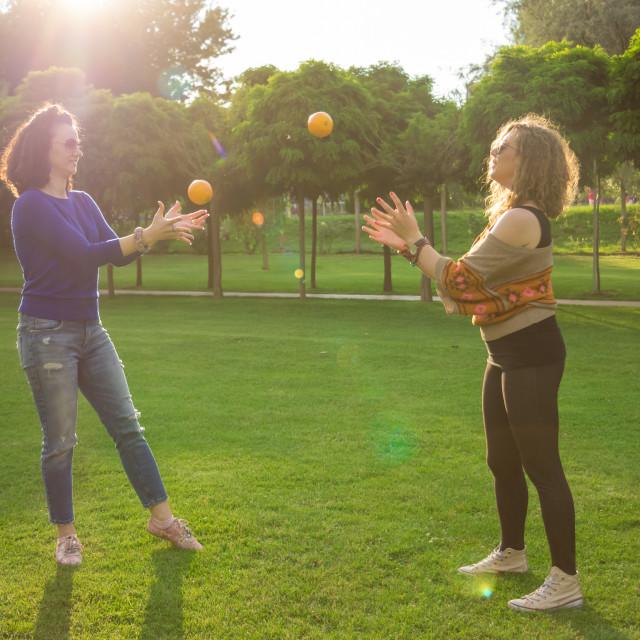 """Two women summer throwing oranges"" stock image"