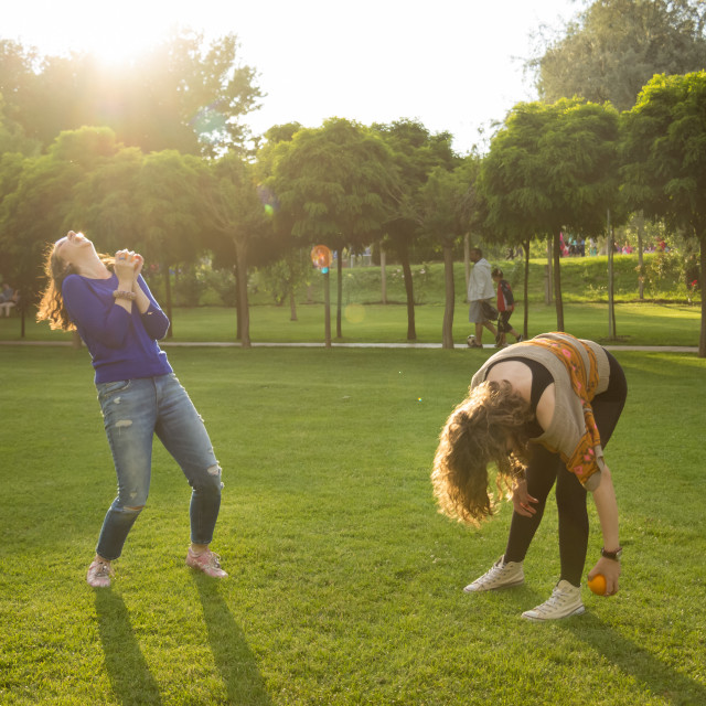 """""""Two women throwing oranges silly funny laughter"""" stock image"""