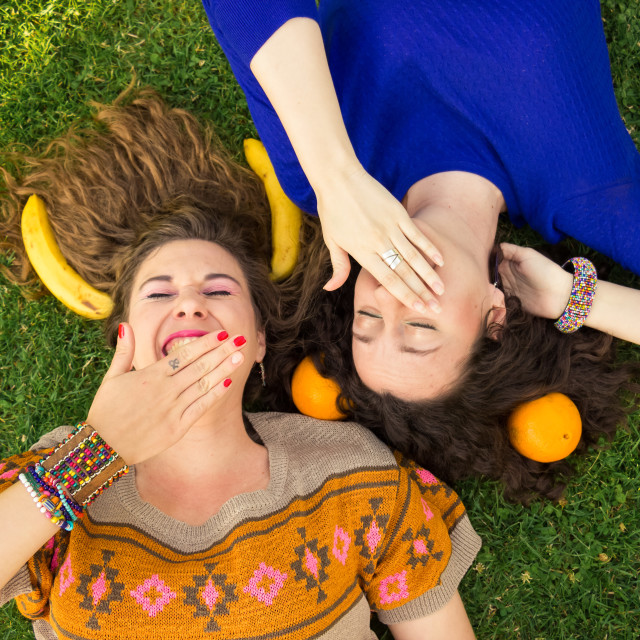 """""""two women young adult girls laughing hands covering mouth"""" stock image"""
