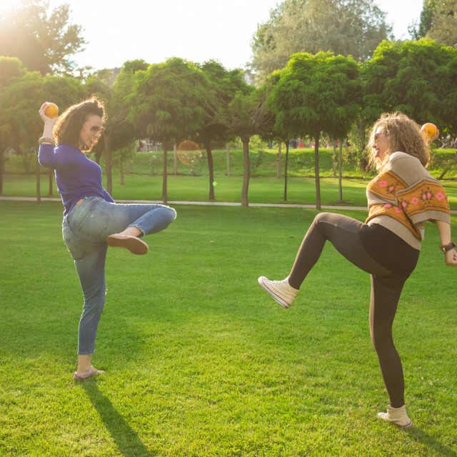 """""""Two young girls throwing oranges funny silly"""" stock image"""