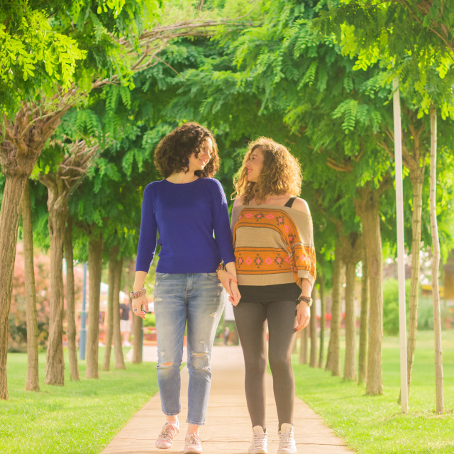 """""""Two young girls walking holding hands looking at each other"""" stock image"""