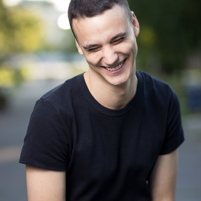 """""""Young man in early 20s laughing smiling"""" stock image"""