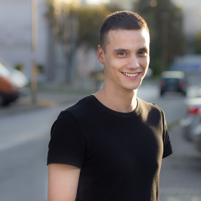 """""""Young man in early 20s smiling portrait outdoors"""" stock image"""