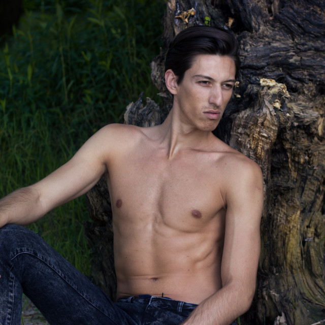 """""""Young man sitting sand posing skinny slim fit abs closeup"""" stock image"""