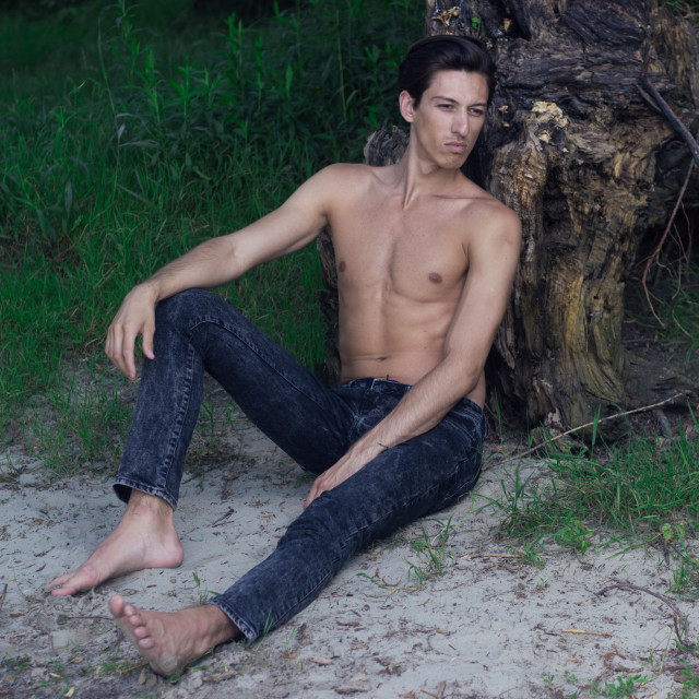 """""""Young man sitting sand posing skinny slim fit abs"""" stock image"""