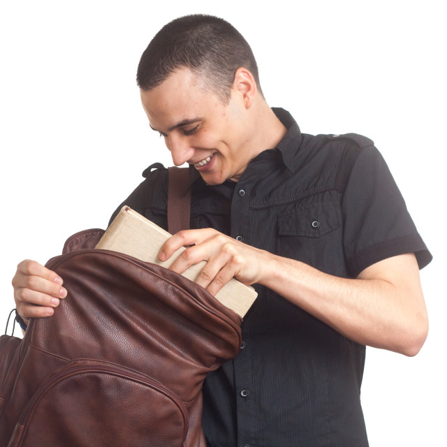 """""""Young student putting/pulling book from bag."""" stock image"""