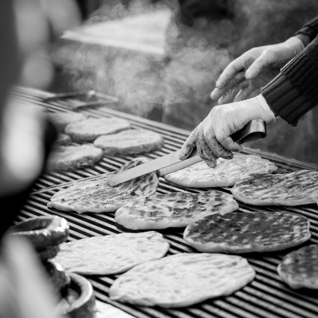 """Roasting outdoors slim breads on barbeque in black and white"" stock image"