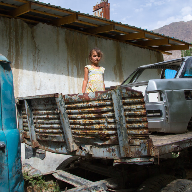 """Tajik girl playing in old cars wrecks, Gorno-Badakhshan autonomous region,..."" stock image"