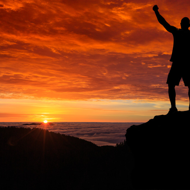 """Man silhouette on the mountain top watching the sunrise over clo"" stock image"