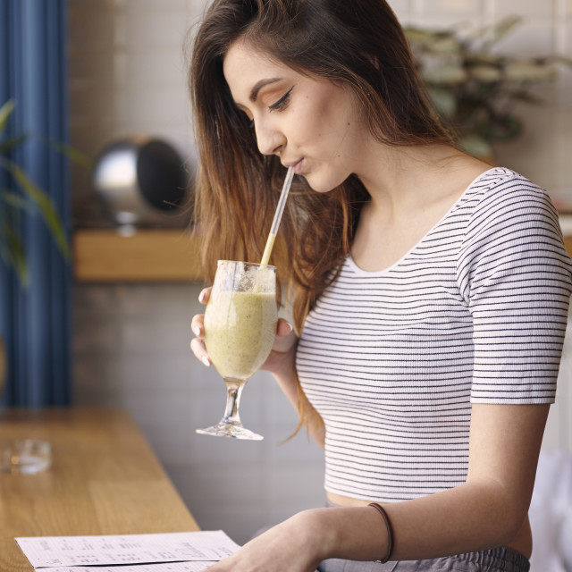 """""""Young Caucasian girl drinking milkshake, sitting in cafe. side view, looking..."""" stock image"""