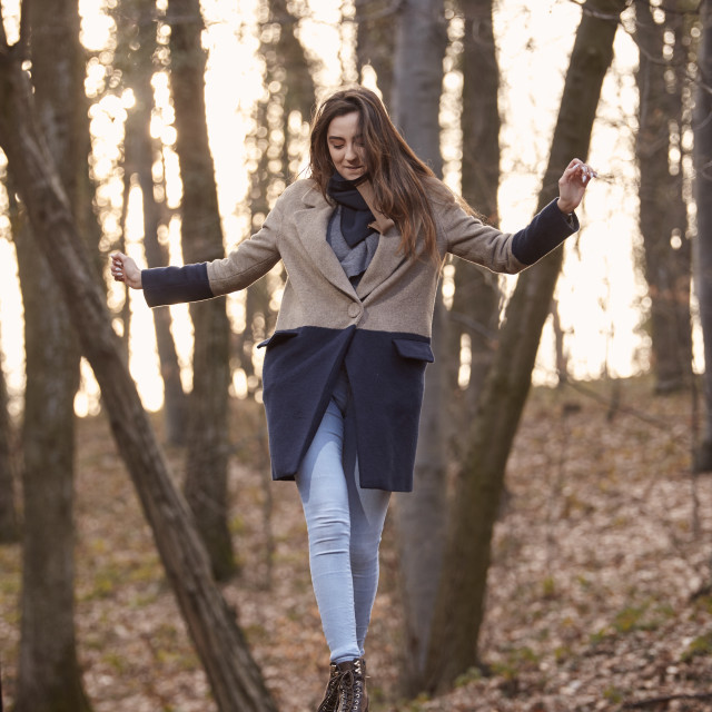 """""""one cute young girl, looking down, standing on table in forest outdoors."""" stock image"""