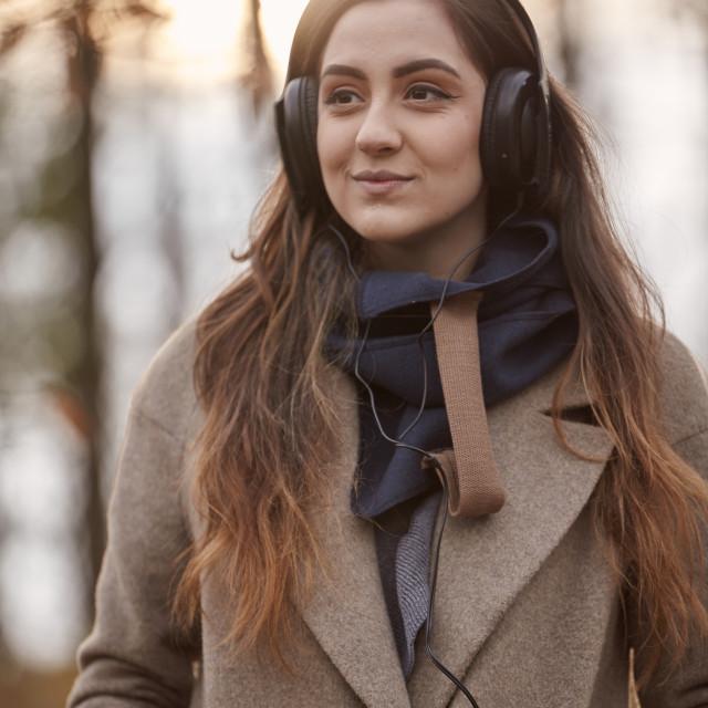 """one young girl, looking away, listening to headphones, winter autumn coat,..."" stock image"