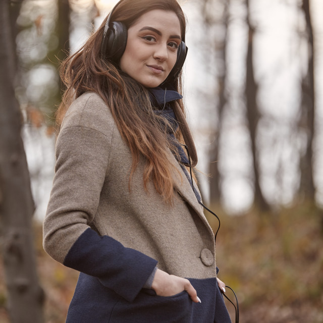 """""""one young woman standing, looking at camera, in forest, wearing winter autumn..."""" stock image"""