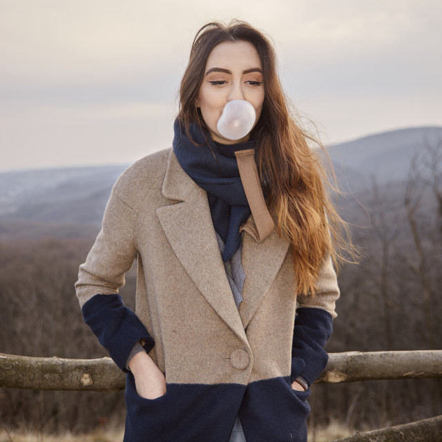 """""""one young cute Caucasian girl, looking away, blowing bubble gum, wearing..."""" stock image"""