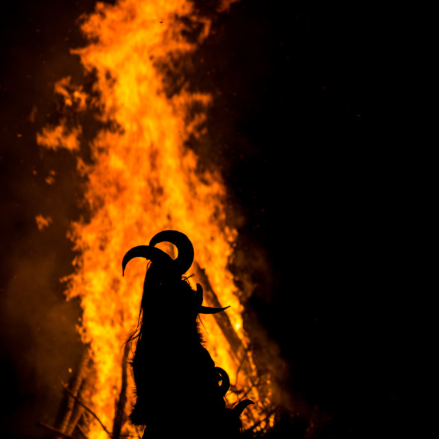 """Dancing around the huge ritual fire in mask with horns"" stock image"