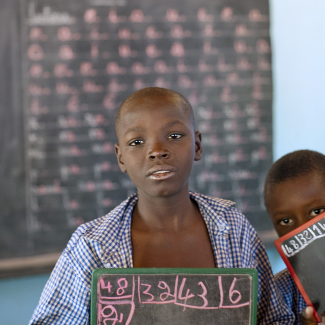 """Pupil with slate board at Ecole Agora, Niamey, Niger"" stock image"