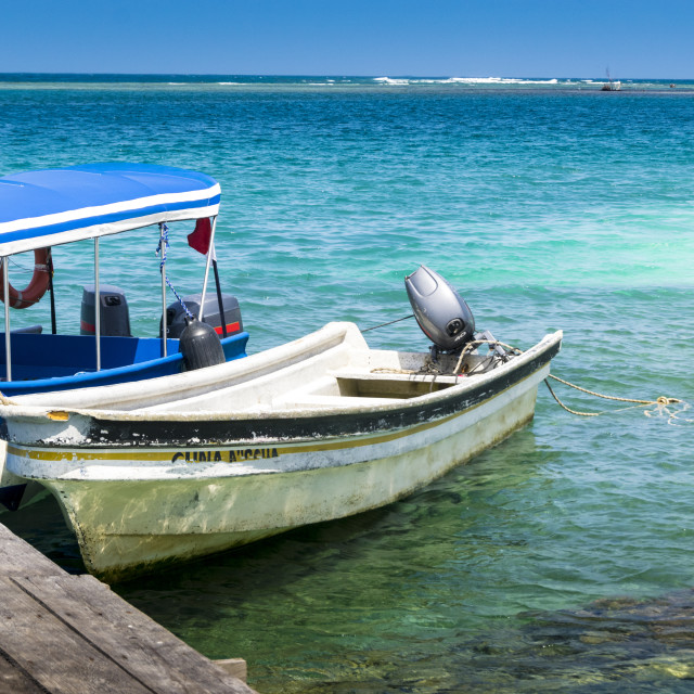 """Two small boats docked in front of the Caribbean island"" stock image"