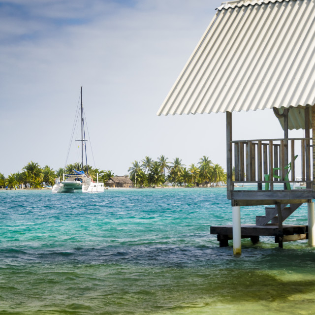 """Small boat in front of the Caribbean island and vacation cabin"" stock image"