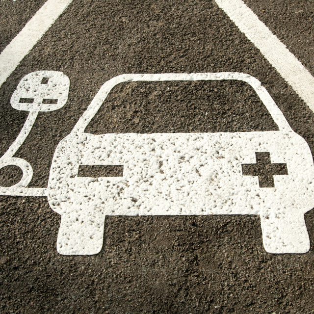 """electric vehicle recharging point sign painted on the road"" stock image"