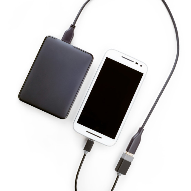"""White smartphone connected to a black hard disk drive with an OT"" stock image"