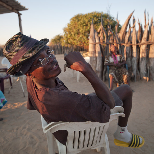"""Ovambo Man On A Plastic Chair, Ruacana Area, Namibia"" stock image"