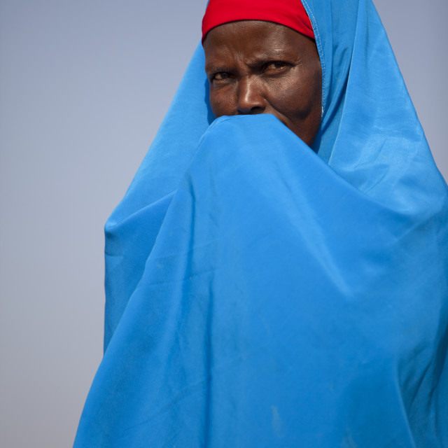"""""""A Woman Wearing A Blue Hijab Is Hiding Her Mouth In Her Hands, Burao, Somaliland"""" stock image"""