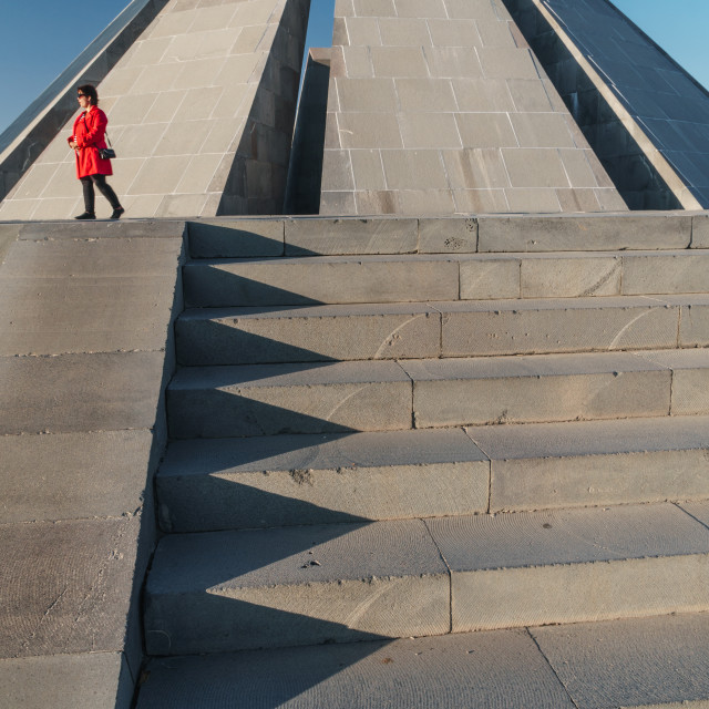 """Woman in red walks past Armenian Genocide Memorial building, Yeravan, Armenia"" stock image"
