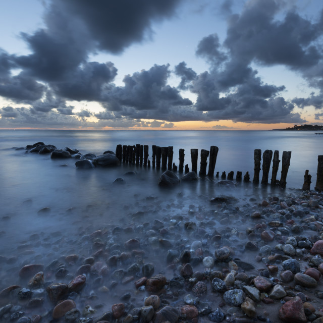 """Old wooden piles going out to sea and pebbles on beach at dawn, Munkerup,..."" stock image"