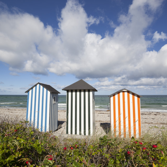 """Colourful beach huts on pebble beach with blue sea and sky with clouds,..."" stock image"