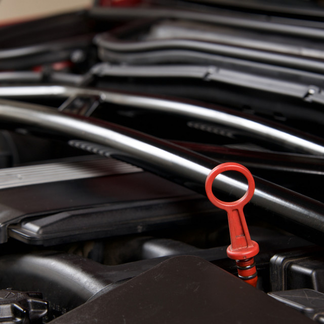 """""""Close up of an oil dipstick in a clean car engine bay"""" stock image"""