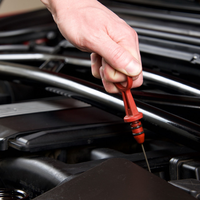 """Hand pulls out oil dipstick in a clean car engine bay"" stock image"
