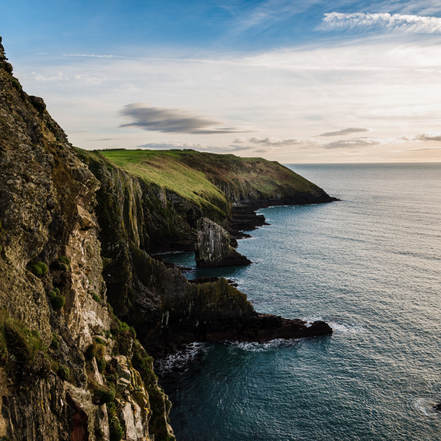 """Scenic view of cliffs in Irish coast with green hills at sunset."" stock image"
