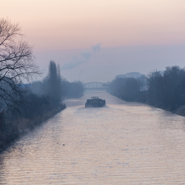 """""""Sunrise over a waterway in Berlin at a misty morning with view to a freighter and a bridge in background."""" stock image"""