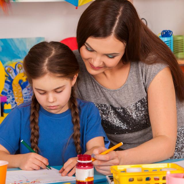 """Children painting finger on easel. Group of kids with teacher."" stock image"