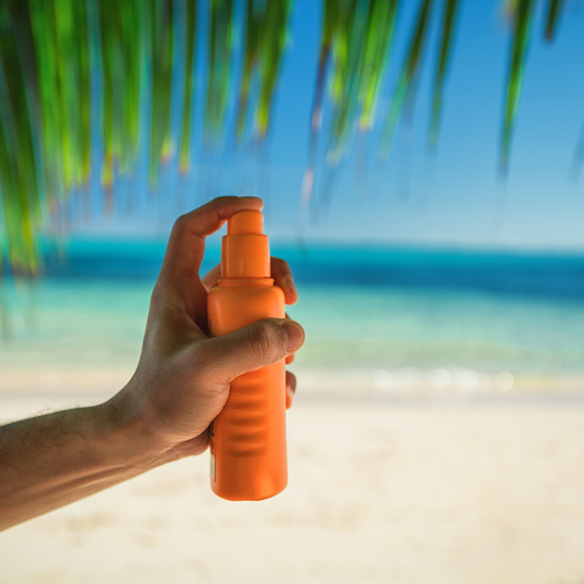 """Bottle of sun protection lotion and palm leaf on the background"" stock image"