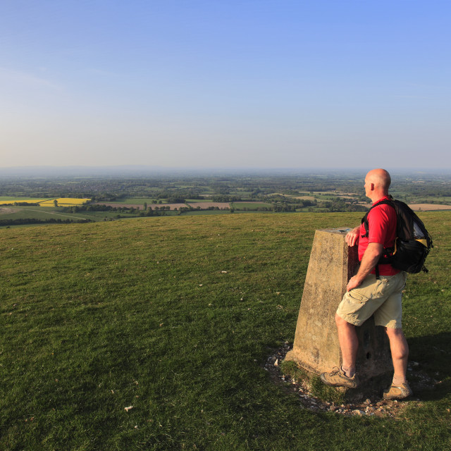 """""""Walker at the Ordinance Survey Trig Point, Chanctonbury Ring, South Downs..."""" stock image"""