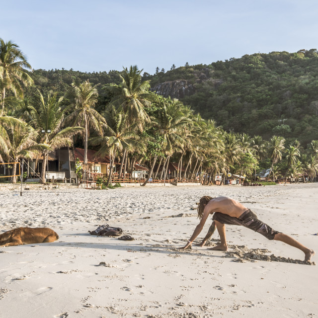 """""""Young man stretching out on a tropical beach in the morning"""" stock image"""