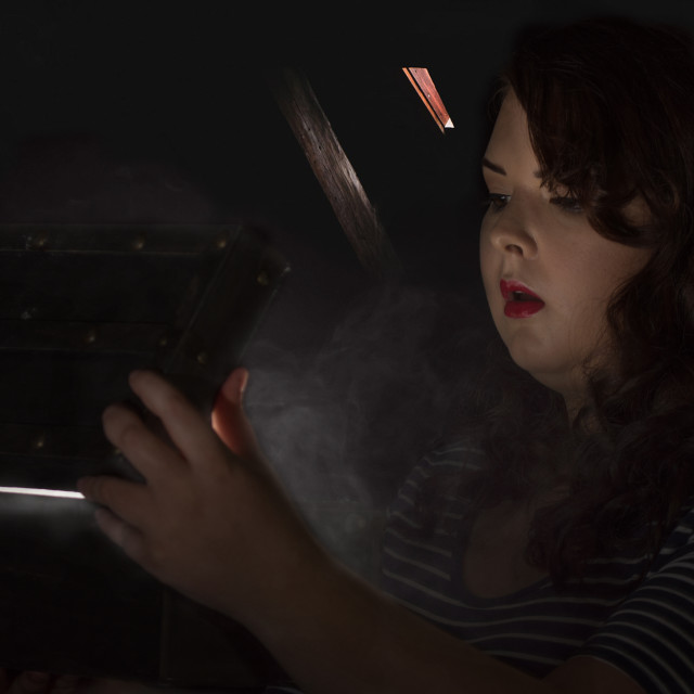 """""""woman opens a box in a attic smoke and light escapes from it"""" stock image"""