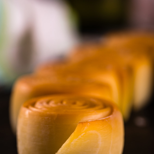 """Detail of the rolled parenica cheese with others in a row"" stock image"