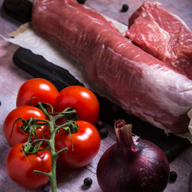 """Few red cherry tomatoes next to pork tenderloin on wooden board"" stock image"