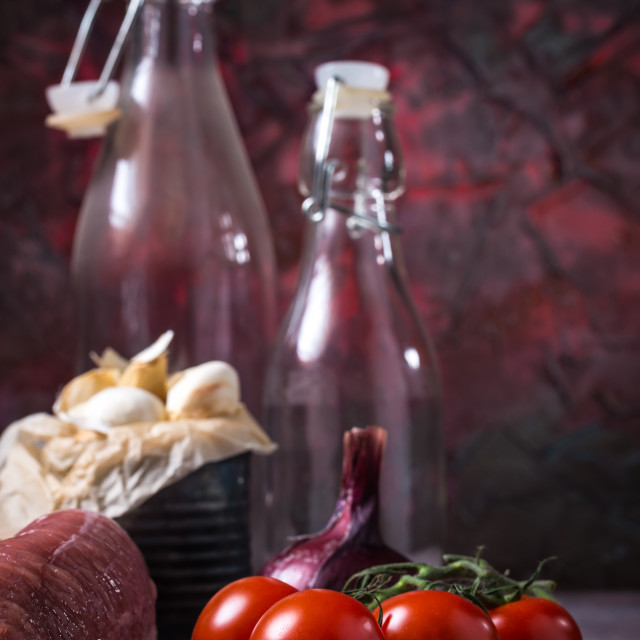"""Red tomatoes next to whole pork tenderloin meat on vintage board and garlic"" stock image"