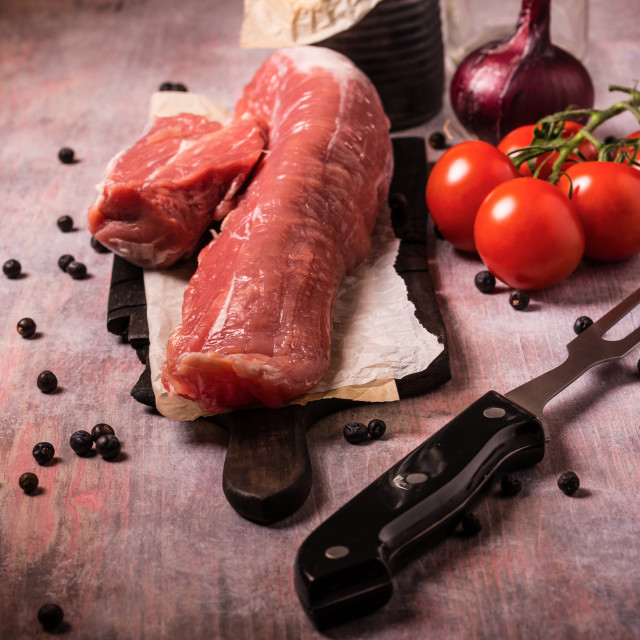 """Pork tenderloin and other ingredients on vintage board"" stock image"