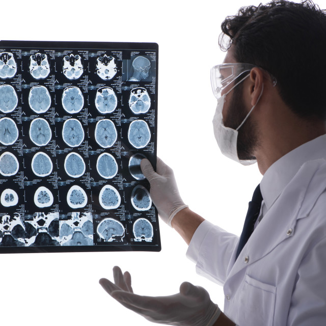 """""""Young doctor looking at x-ray images isolated on white"""" stock image"""