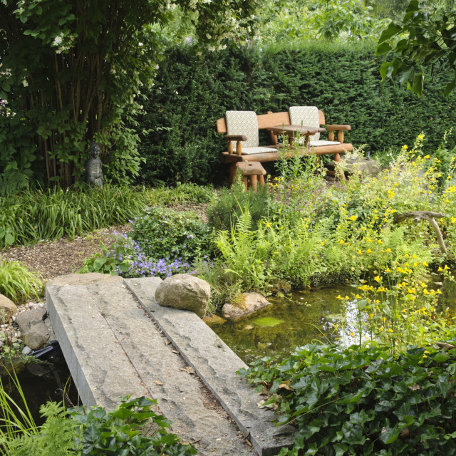 """Garden bench at a pond with a stone bridge. Design: Marianne and Detlef Luedke"" stock image"